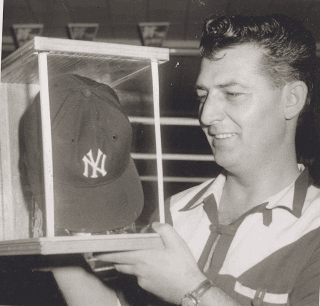 Man in polo holding a Yankee hat in a glass case