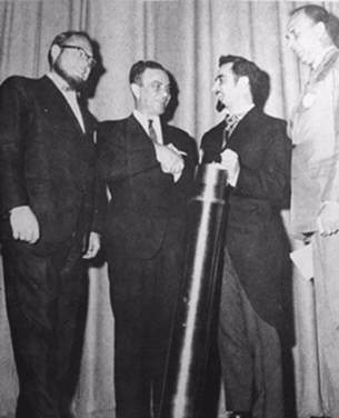 4 men and one of them holding a metal cylindrical capsule.