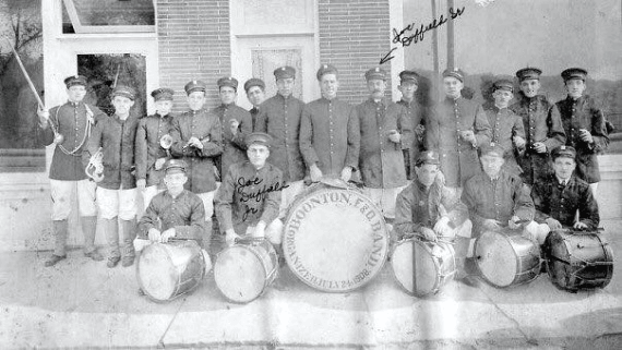 black and white photo of males in Harmony Senior Drum Corp with drums